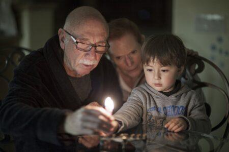 Jewish Family lighting Hanukkah Candles (iStock/Enzo Nguyen@Tercer Ojo Photography)